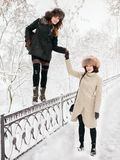 Adorable happy young brunette women holding hands in fur hat having fun snowy winter park forest in nature Royalty Free Stock Photos