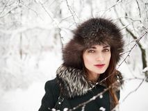 Adorable happy young brunette woman in fur hat having fun snowy winter park forest in nature Stock Images