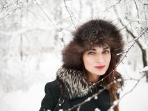 Adorable happy young brunette woman in fur hat having fun snowy winter park forest in nature Stock Photography