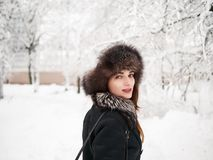 Adorable happy young brunette woman in fur hat having fun snowy winter park forest in nature Royalty Free Stock Photos