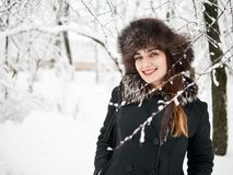 Adorable happy young brunette woman in fur hat having fun snowy winter park forest in nature Stock Photos