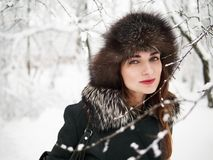 Adorable happy young brunette woman in fur hat having fun snowy winter park forest in nature Royalty Free Stock Images