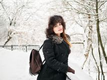 Adorable happy young brunette woman in fur hat having fun snowy winter park forest in nature Royalty Free Stock Photography