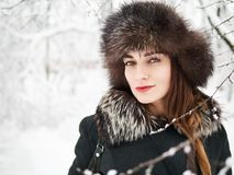Adorable happy young brunette woman in fur hat having fun snowy winter park forest in nature Stock Photo