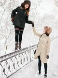 Adorable happy young brunette women holding hands in fur hat having fun snowy winter park forest in nature Royalty Free Stock Image