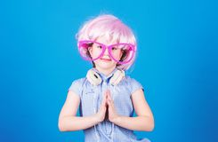 Adorable headset user with praying hands. Small child wearing adjustable white headset and pink hair wig. Little girl. With wireless bluetooth headset. Cute kid royalty free stock images