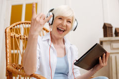 Adorable hilarious elderly woman enjoying cool song Stock Image