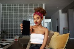 Adorable hipster dark-skinned woman with Afro hairstyle holding hands mobile phone, smiling, sitting on the couch at. Home stock images