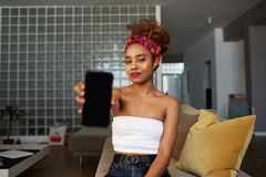 Adorable hipster dark-skinned woman with Afro hairstyle holding hands mobile phone, smiling, sitting on the couch at. Home royalty free stock image