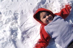 Adorable Hispanic Boy. Darling little boy laying on the snow Royalty Free Stock Photography