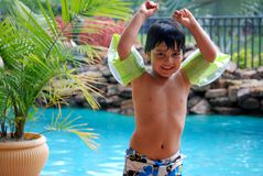 Adorable Hispanic boy showing his muscles. A four year old Hispanic boy shows off his muscles by the pool stock photography