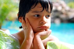 Adorable Hispanic child daydreaming by pool. A four year old boy by a luxurious pool, daydreaming Stock Photos