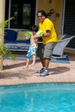 Adorable Hispanic child with his father by pool Stock Photography