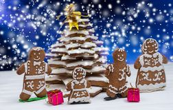 Adorable homemade gingerbread Christmas tree with cute gingerbread family with gifts. On snowfall background. Mockup for seasonal offers and holiday post card Stock Image
