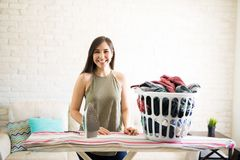 Adorable housewife with laundry bag. Cute smiling woman all set to iron clothes kept in basket at home Stock Photos