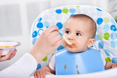 Adorable hugry baby child likes to eat Stock Photos