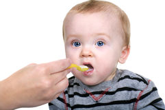 Adorable Hungry Boy. Beautiful baby being feed rice cereal with a yellow spoon Royalty Free Stock Photography