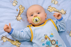 Adorable infant. Four months old infant dressed in blue with her arms wide open waiting for her mummy royalty free stock photography