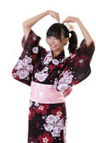 Adorable japanese young girl. Put hand on head against white background Stock Photos
