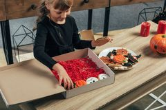Adorable kid arranging themed halloween cookies at wooden tabletop. At home stock photography