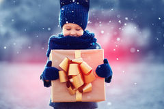 Adorable kid with big gift box under a snowfall. Focus on gift box Stock Photos