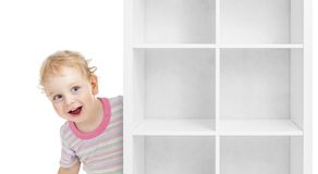 Adorable kid boy behind empty white shelves. Isolated Royalty Free Stock Photography