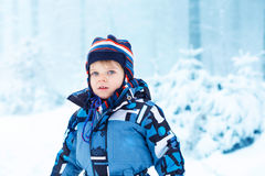 Adorable kid boy having fun with snow outdoors Stock Images