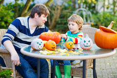 Adorable kid boy and his father  making jack-o-lantern for hallo. Adorable kid boy and his father making jack-o-lantern for halloween in autumn garden, outdoors Stock Photography