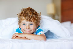 Adorable kid boy after sleeping in his white bed Royalty Free Stock Image