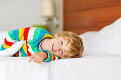Adorable kid boy after sleeping in his white bed stock photo