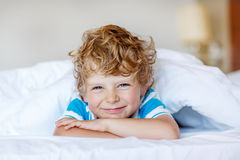 Adorable kid boy after sleeping in his white bed with toy Royalty Free Stock Photos