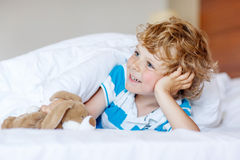 Adorable kid boy after sleeping in his white bed with toy Royalty Free Stock Photo