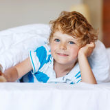 Adorable kid boy after sleeping in his white bed with toy Stock Image
