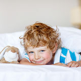 Adorable kid boy after sleeping in his white bed with toy Stock Photo