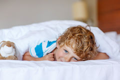 Adorable kid boy after sleeping in his white bed with toy Stock Photos