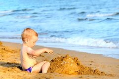 Adorable kid building sandcasle Royalty Free Stock Image