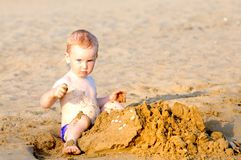 Adorable kid building sandcasle Stock Image