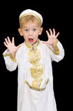 Adorable kid with facial expression. An adorable little boy dressed in Arabian thobe, isolated on black Royalty Free Stock Image