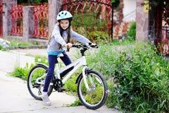 Adorable kid girl in blue helmet riding her bike Royalty Free Stock Photos