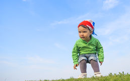 Adorable kid girl jumping and having fun outdoors in the sunny day Stock Images