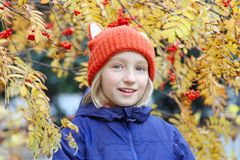 Cheerful kid girl smiling, the child is dressed in a funny knitted warm hat with ears, looks like a fox. Autumn, outdoors portrait. Adorable kid girl smiling Stock Photo