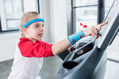 Adorable kid girl in sportswear training on treadmill at gym. Children sport concept Royalty Free Stock Photo
