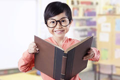 Adorable kid holding textbook in classroom Stock Image