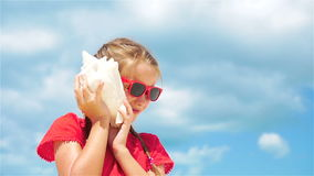Adorable kid listening a big seashell on white tropical beach. SLOW MOTION. Portrait of adorable little girl with a seashell stock video
