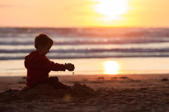 Adorable kid, playing on the beach on sunset Royalty Free Stock Photos