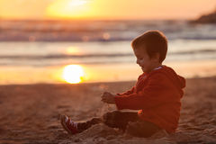 Adorable kid, playing on the beach on sunset time Royalty Free Stock Image