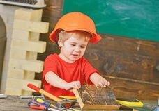 Adorable kid playing with working tools. Boy in orange protective helmet holding a wooden block. Little builder royalty free stock photography