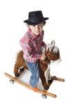 Adorable kid riding a toy horse Stock Photos