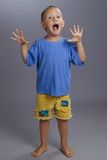Adorable kid screaming  in studio on grey backgr Royalty Free Stock Photos