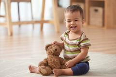 Adorable kid. Smiling adorable kid sitting on the floor with teddy bear Royalty Free Stock Photography